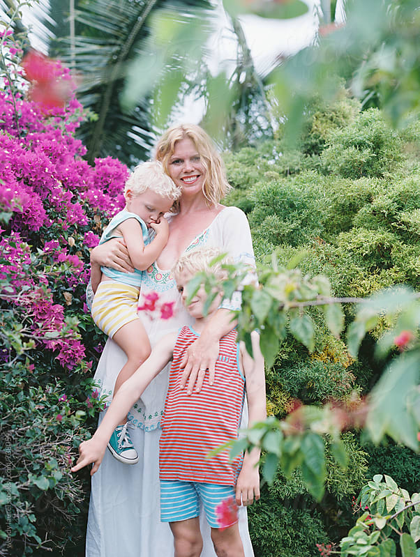 pretty blonde  mom and two sons in striped pajamas standing in garden on film by wendy laurel for Stocksy United
