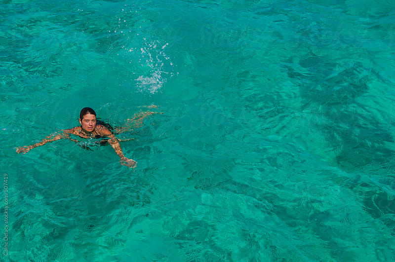 Young Female, bruneete swims in crystal clear water by Caine Delacy for Stocksy United
