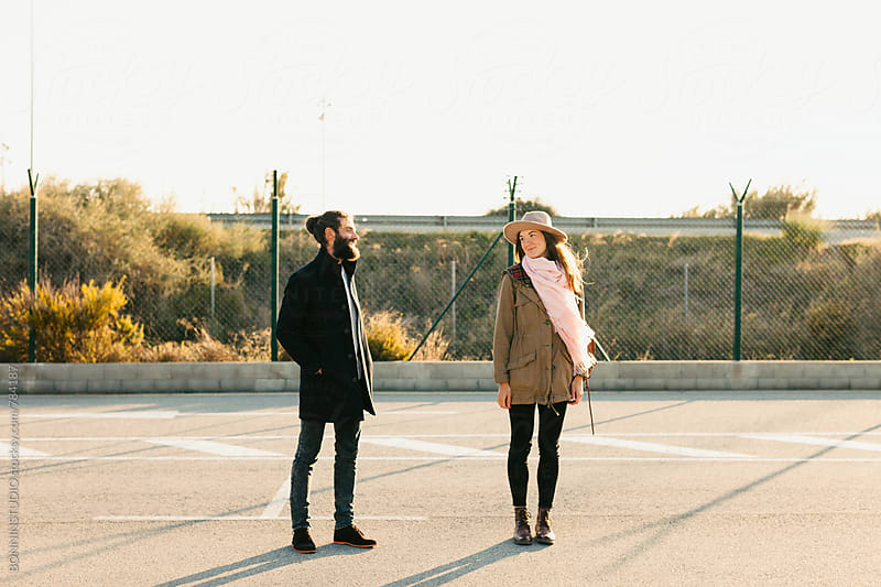 Smiling hipster couple standing outside on a sunny day. by BONNINSTUDIO for Stocksy United