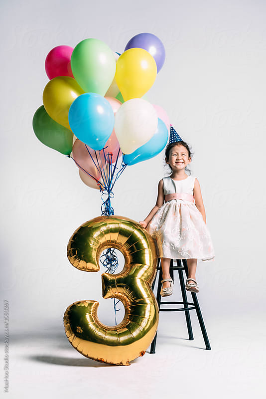 Adorable little girl at her three years birthday party by MaaHoo Studio for Stocksy United