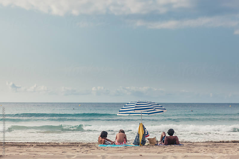 Father and his sons lying on the beach under a parasol in the summer by Cindy Prins for Stocksy United