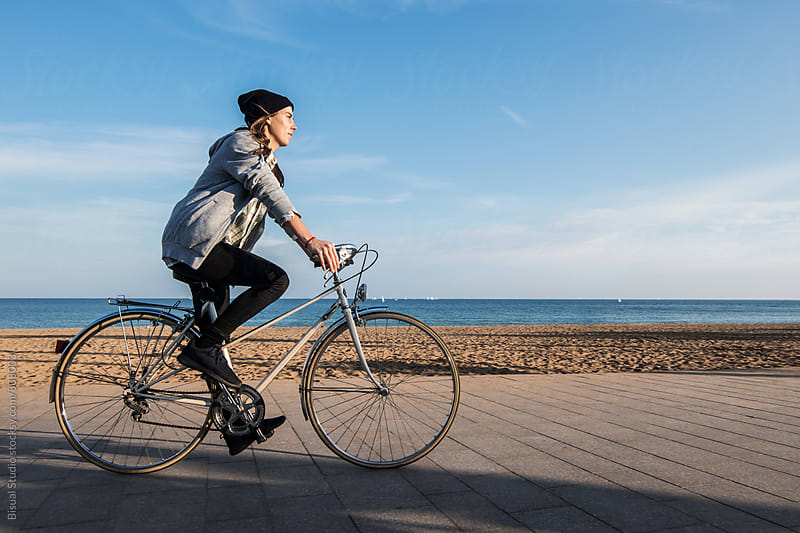 Young woman riding a bicycle on the beach, Barcelona by Bisual Studio for Stocksy United