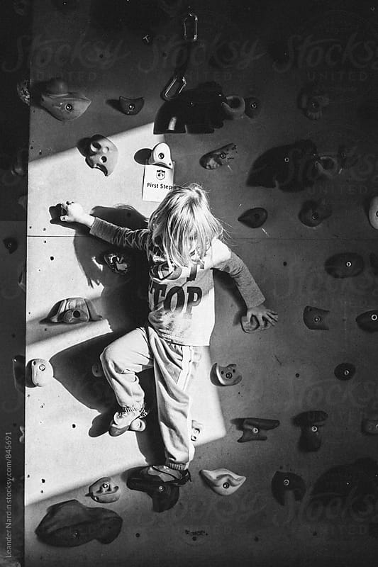young boy with long hair on an indoor climbing wall - black and white by Leander Nardin for Stocksy United