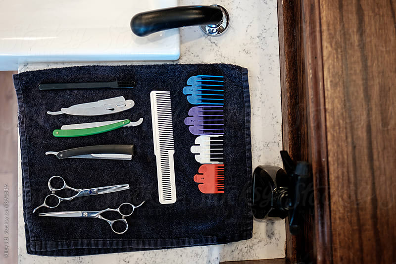 A barber's tools laid out on a towel next to a sink. by Riley J.B. for Stocksy United