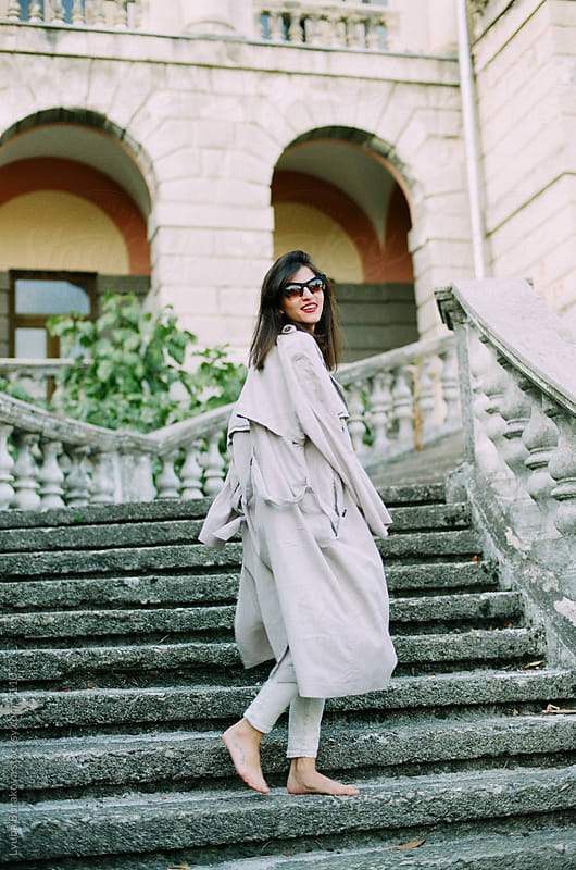 Happy woman wearing grey trench and sunglasses by Liubov Burakova for Stocksy United