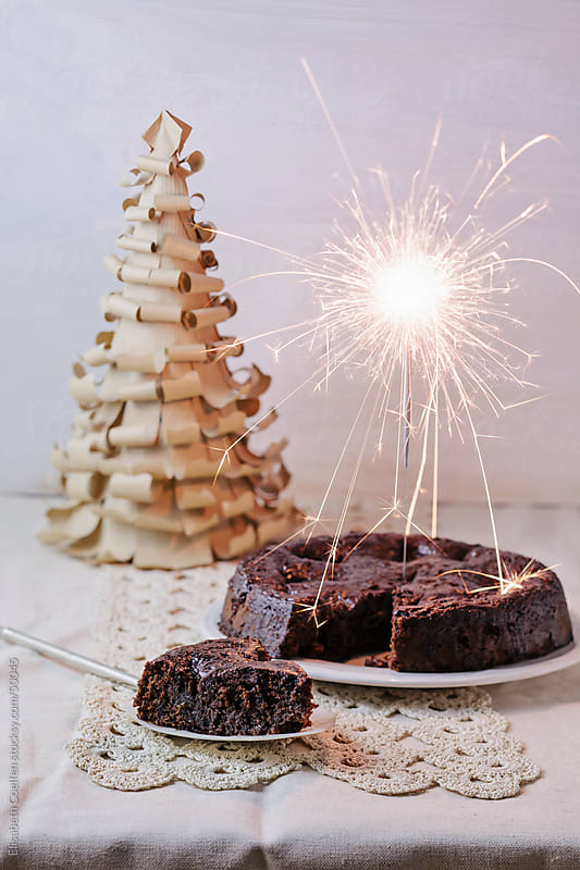 Moist chocolate cake with prunes soaked in cognac, a sparkler and a DIY Christmas tree by Elisabeth Coelfen for Stocksy United