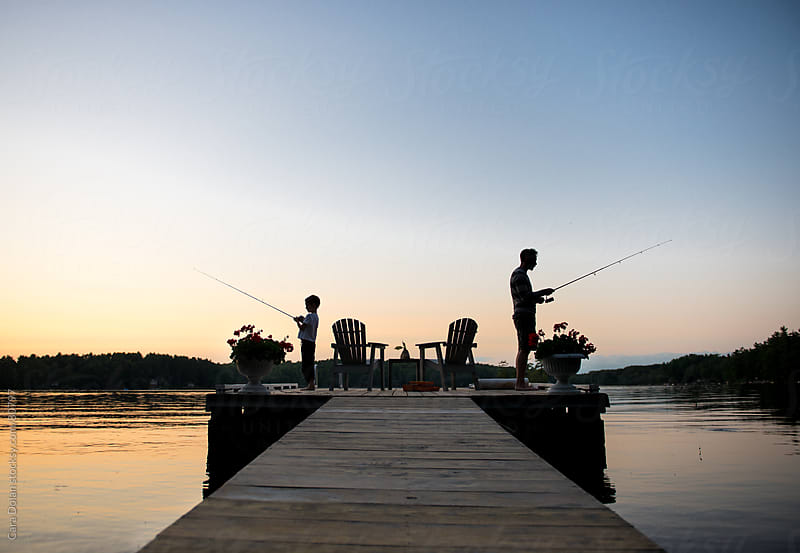 Father and son fish on a dock at sunset by Cara Dolan for Stocksy United