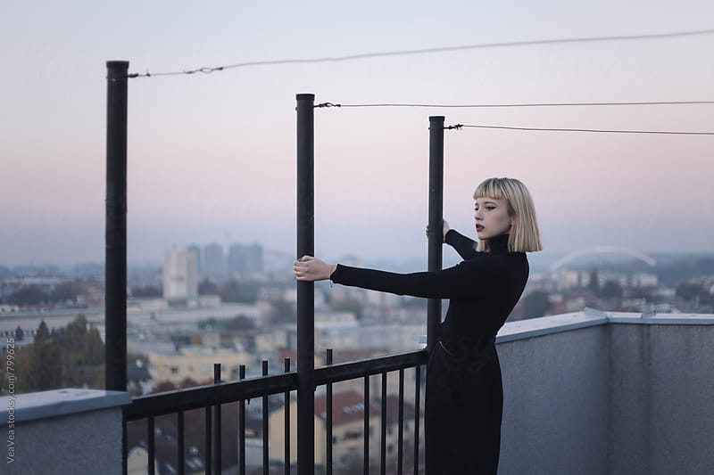 Stylish blonde woman on the roof of the building during sunset  by Marija Mandic for Stocksy United