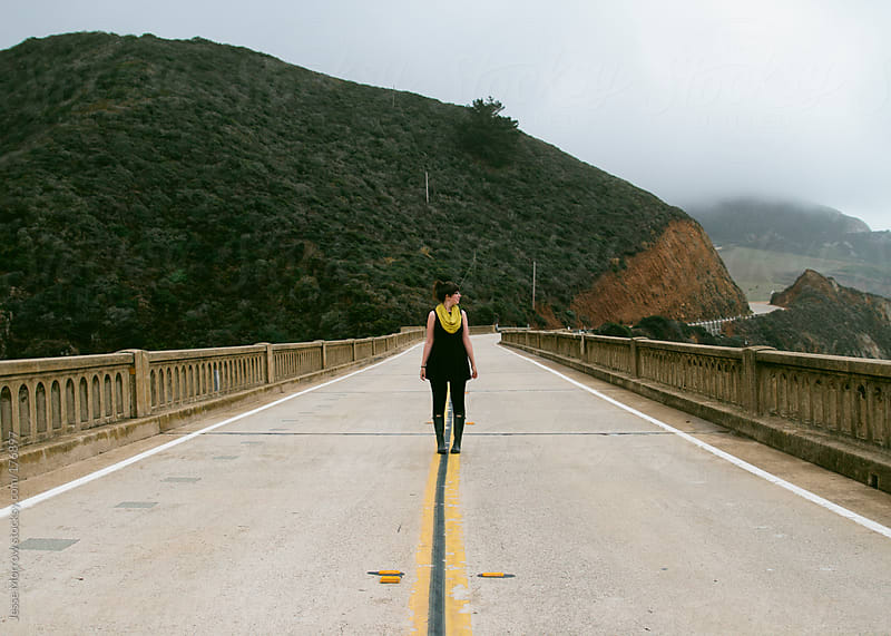 young woman stands in middle of bridge by Jesse Morrow for Stocksy United
