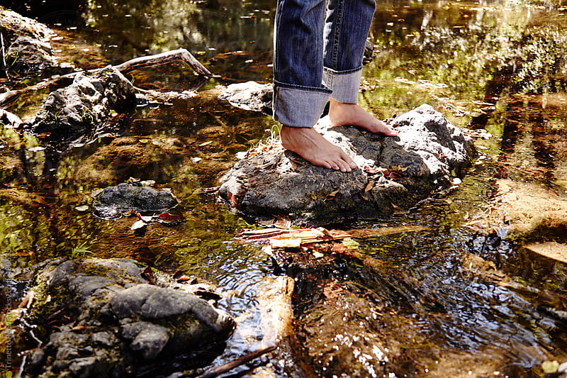 Woman's feet on rocks in a stream.   by Trinette Reed for Stocksy United