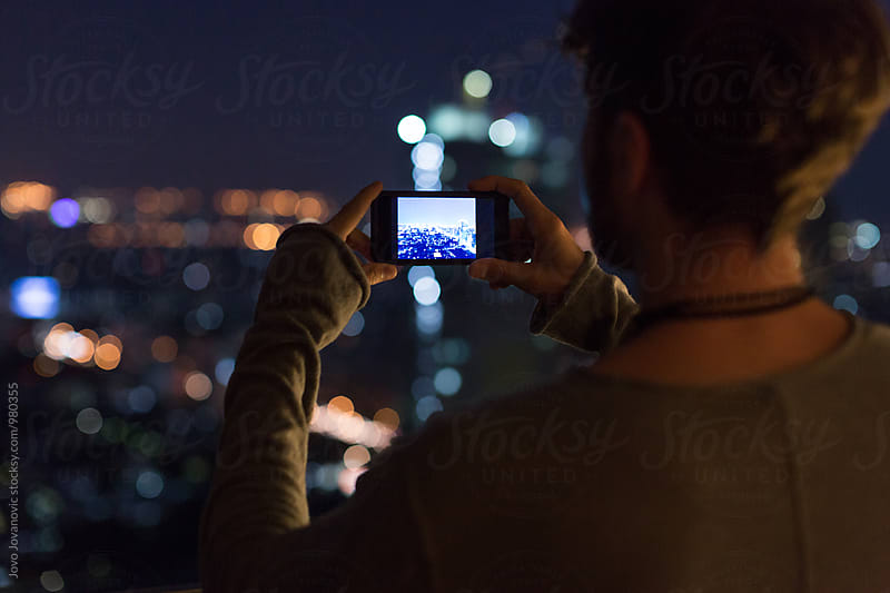 Rear view of a man taking a photo at night  by Jovo Jovanovic for Stocksy United