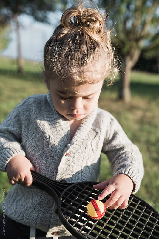 Toddler playing with a plastic racket and ball by Lior + Lone for Stocksy United