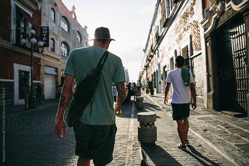Back view of two young men walking down a picturesque stone street by Alejandro Moreno de Carlos for Stocksy United