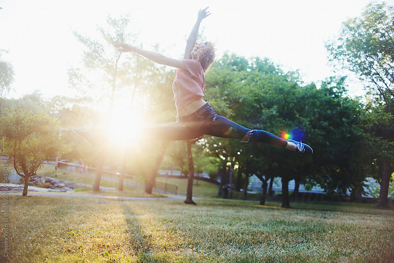 A young woman dancing in a park in the summertime by Chelsea Victoria for Stocksy United