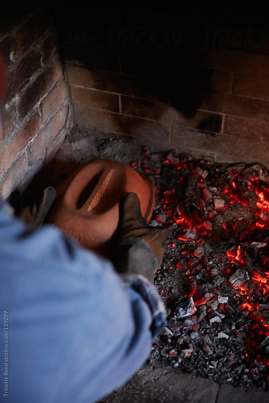 Man cooking baked apple dessert on hearth fireplace inside his cabin by Trinette Reed for Stocksy United