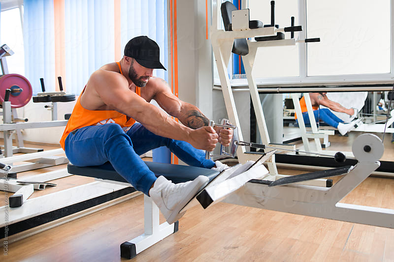 Bodybuilder training at the rowing machine at the gym by RG&B Images for Stocksy United
