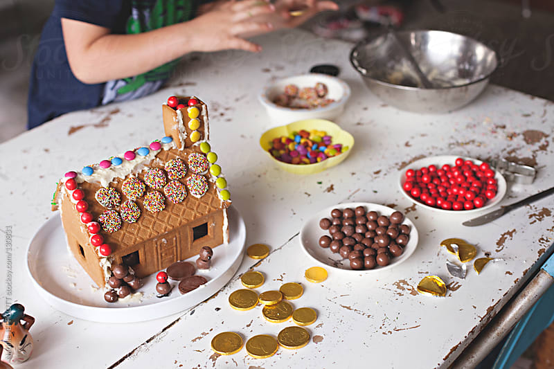 decorating a gingerbread house for Christmas with children. by Natalie JEFFCOTT for Stocksy United