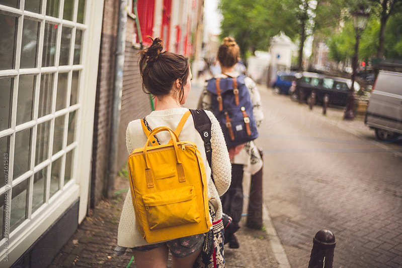 girl walking with yello backpack  by Sam Hurd Photography for Stocksy United