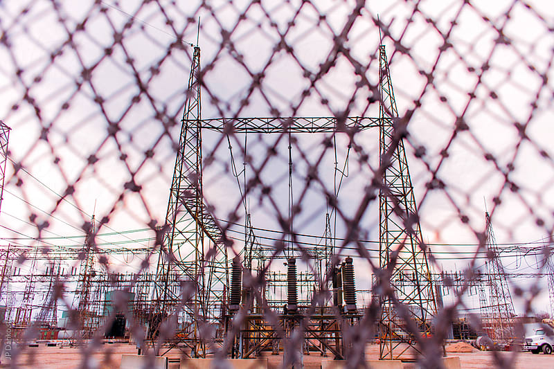 High Tension Transmisison Lines In Restricted Area Behind Fence by JP Danko for Stocksy United