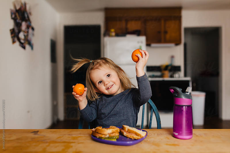 Cute toddler girl eating lunch and playing oranges at the kitchen table. by Jessica Byrum for Stocksy United