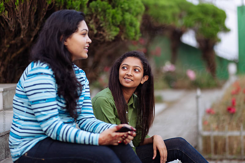 Friends talking to each other sitting in the park by Saptak Ganguly for Stocksy United