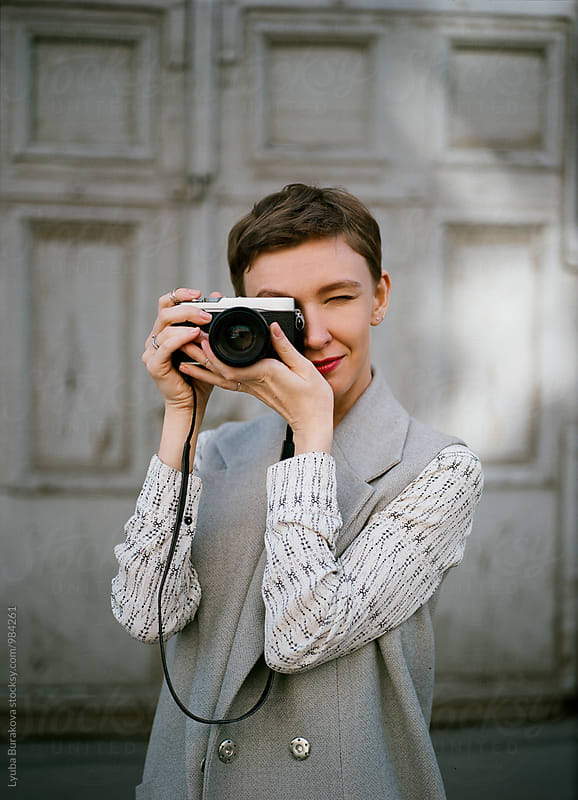 Young woman taking a photo by Liubov Burakova for Stocksy United