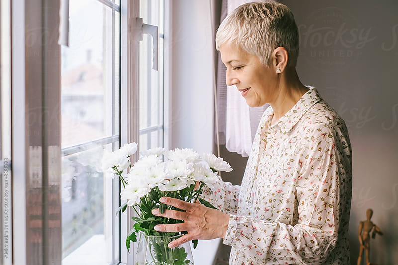 Senior Woman Arranging the Flowers at Home by Aleksandra Jankovic for Stocksy United