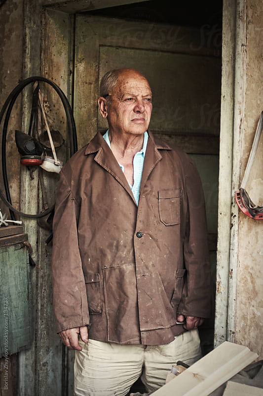 Portrait of an elderly craftsman standing at the door of his workshop by Borislav Zhuykov for Stocksy United