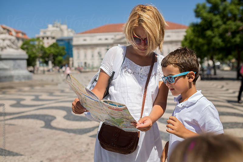 Family looking for an location on map. by Dejan Ristovski for Stocksy United