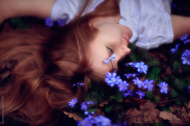 Young woman lying down in spring blue flowers. by Ilya for Stocksy United