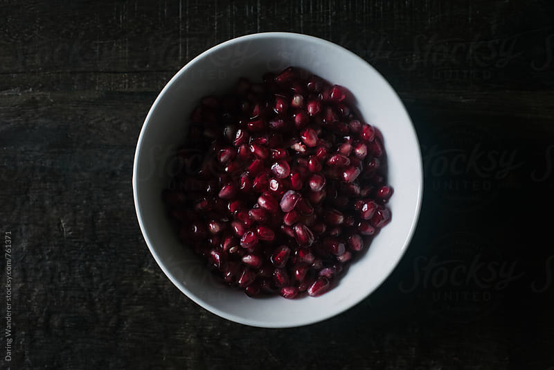 Pomegranate seeds in white bowl on dark wood table by Daring Wanderer for Stocksy United