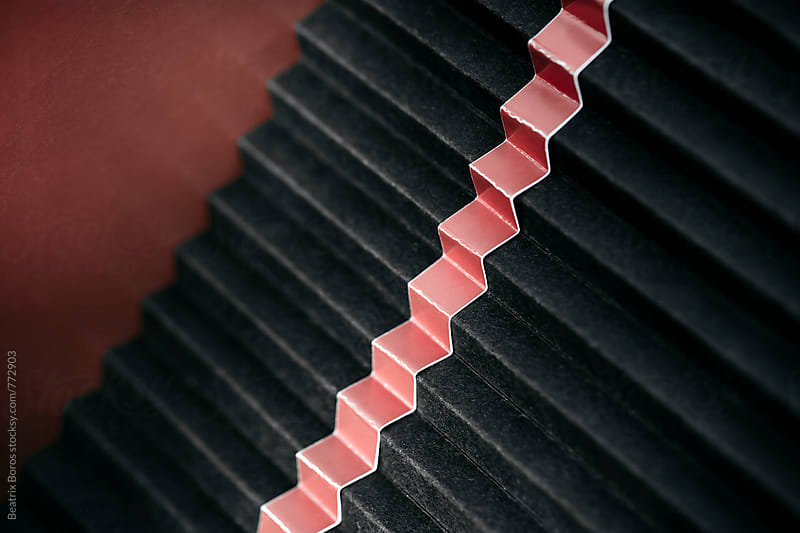 Black stairs with a pink stripe in the middle by Beatrix Boros for Stocksy United
