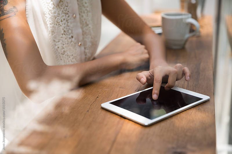 Young woman using tablet in coffee shop by Jovo Jovanovic for Stocksy United