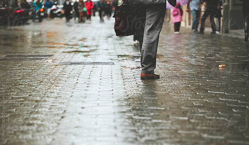 Businessman with briefcase walking down the street. Barcelona streets on rainy day. by BONNINSTUDIO for Stocksy United