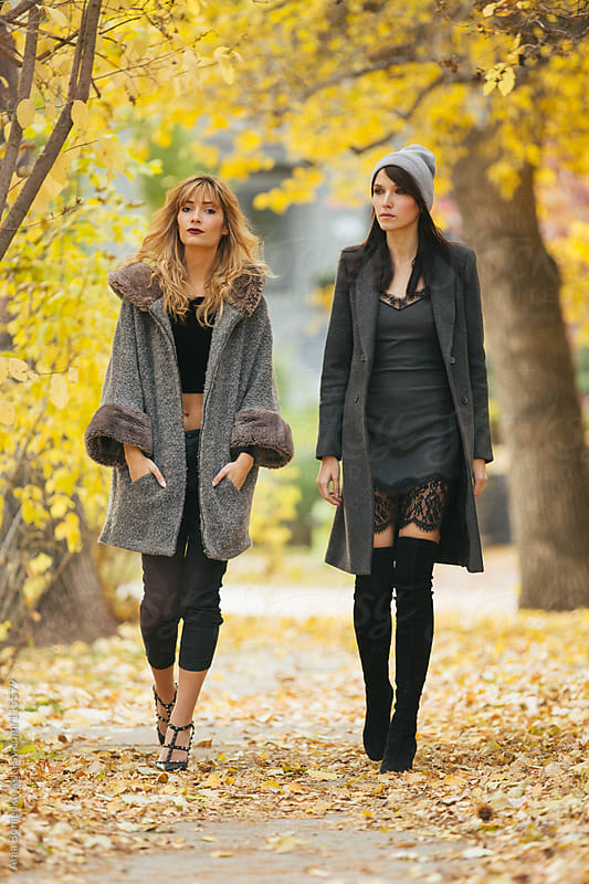 Two stylish women dressed for fall walking toward the camera by Ania Boniecka for Stocksy United
