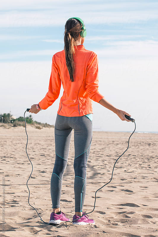 Sporty woman. Young woman looking the sea with a skipping rope.  by BONNINSTUDIO for Stocksy United