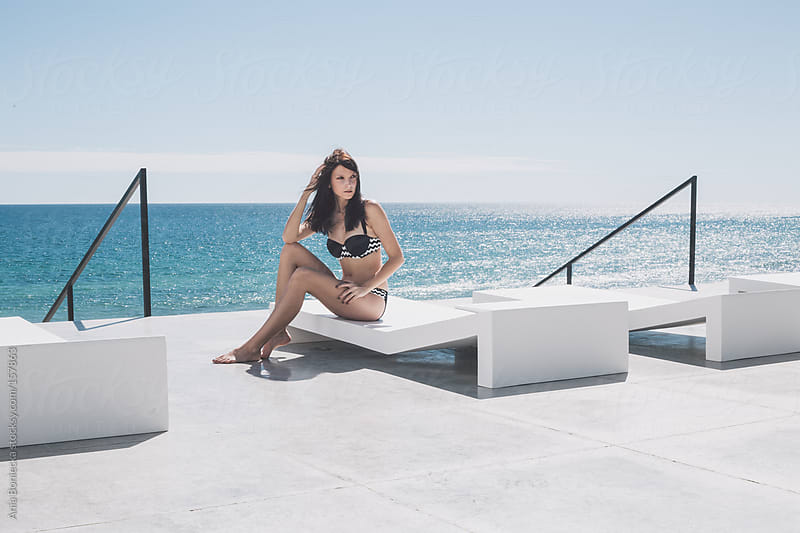 A beautiful woman sitting on a modern patio overlooking the ocean by Ania Boniecka for Stocksy United