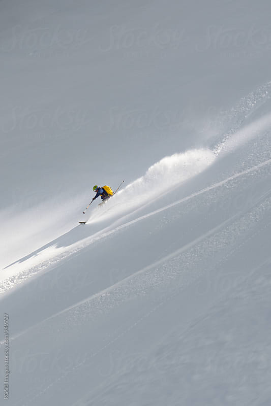 Skier riding downhill with speed splashing with snow by RG&B Images for Stocksy United