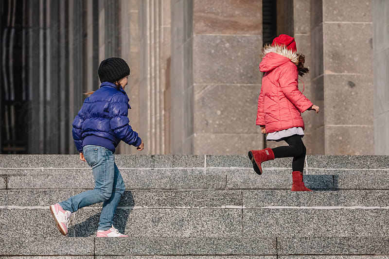 Two young happy children (girls) playing in the city together by Ilya for Stocksy United