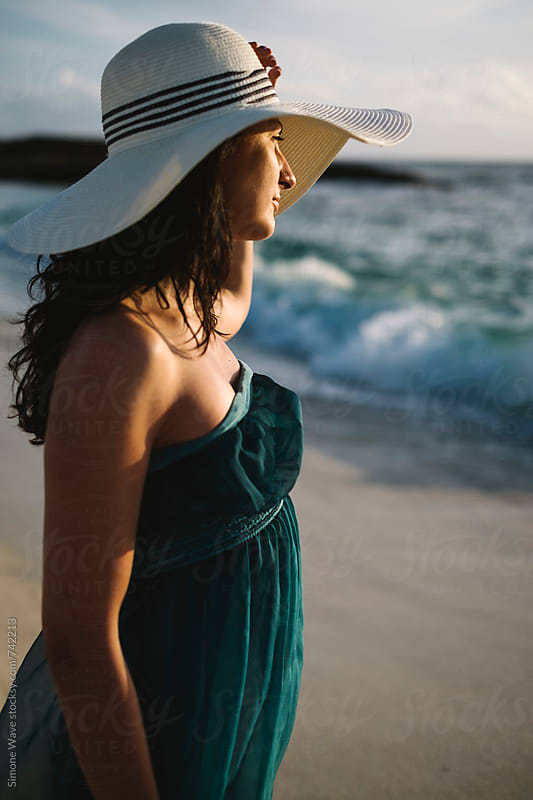 Beautiful young woman with hat on the beach by Simone Becchetti for Stocksy United
