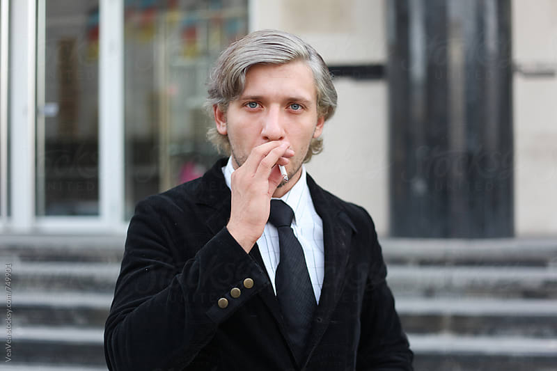 Businessman smoking a cigarette and looking at camera by Marija Mandic for Stocksy United