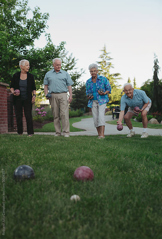 Group of happy, healthy caucasian seniors playing fun game of bocce ball outside by Rob and Julia Campbell for Stocksy United