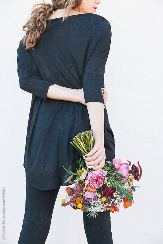 Woman wearing black holding a bouquet of wilting flowers on white background. by RZ CREATIVE for Stocksy United