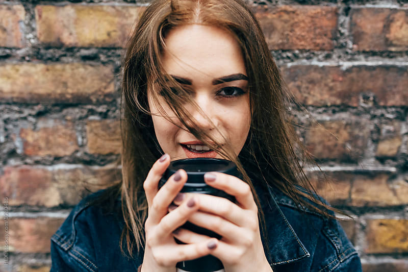 Young Beaufitul Woman Holding a Coffee To Go by Mattia Pelizzari for Stocksy United