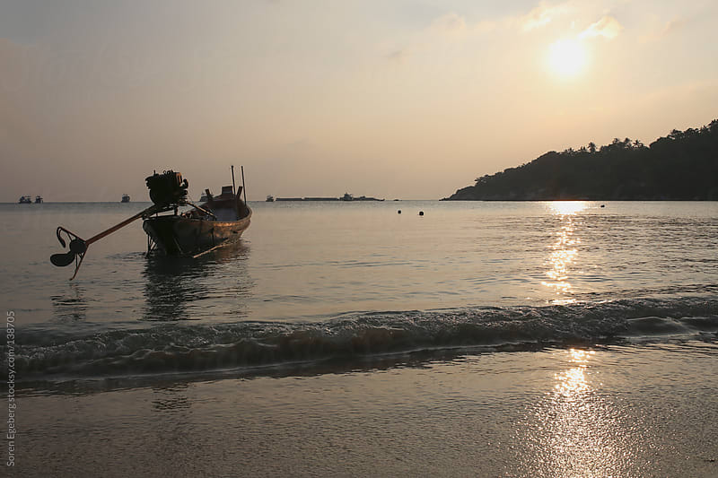 Local longtail boat on the beach at sunset in Thailand by Soren Egeberg for Stocksy United