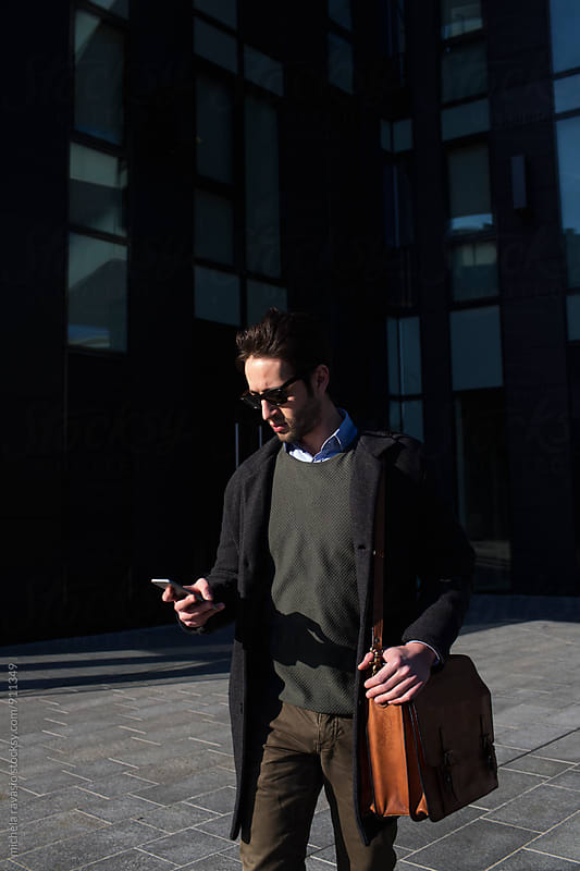 Young man holding his cell outdoors office building by michela ravasio for Stocksy United