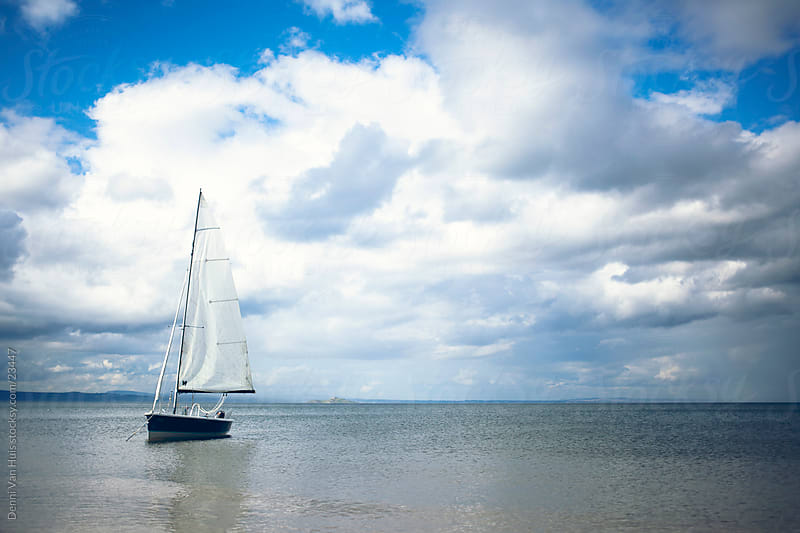 Floating sailboat on a calm ocean by Denni Van Huis for Stocksy United