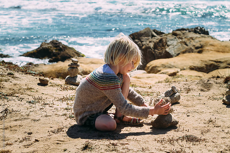 blond child stacking cairns by Jess Lewis for Stocksy United