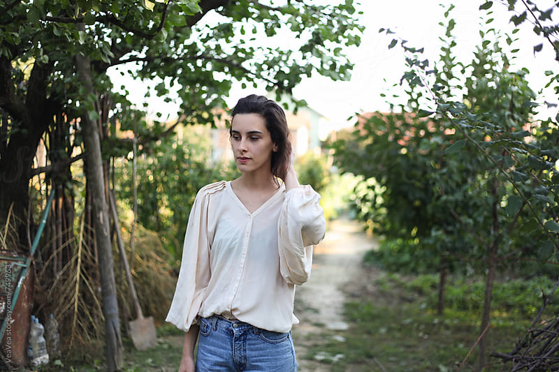 Young woman in the countryside garden  by Marija Mandic for Stocksy United