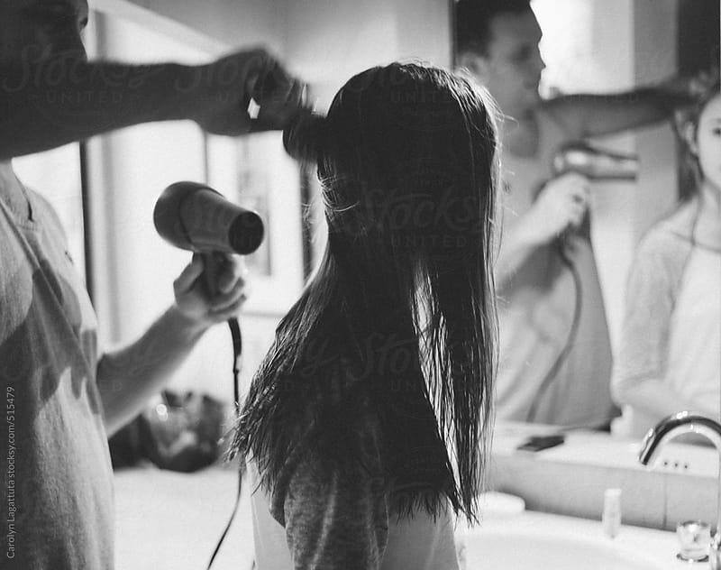 Father drying his daughter's hair in the bathroom by Carolyn Lagattuta for Stocksy United